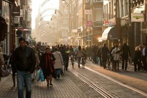 Rue commerçante piétonnière partagée avec un tram à Amsterdam